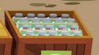 Crate filled with jars of applesauce S9E26