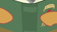 Quibble with his face behind a book S9E6