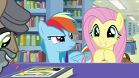 Rainbow looks at grinning Fluttershy S9E21