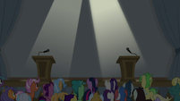 Twin spotlights shine on the stage S8E16