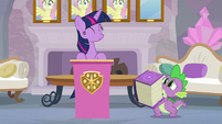 Spike carrying the School of Friendship rule book S8E9