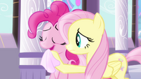 Fluttershy wiping Pinkie's mouth with a napkin S4E01