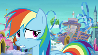 Rainbow looking at the hotel behind her S8E5