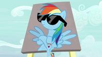 Rainbow Dash under a large billboard of herself S7E14