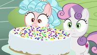 Sweetie and Cozy look at rainbow-sprinkled cake S8E12