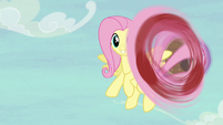 Fluttershy winds up before flinging the ball S6E18