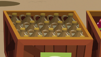 Crate filled with jugs of apple cider S9E26