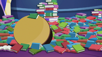 Mess of library books and table S6E21