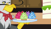 Gustave le Grand holding tray of jeweled cupcakes S5E10