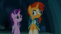 Starlight and Sunburst walk through a dim cave S7E24