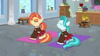 Cheer ponies sitting on yoga mats S9E15