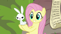 Angel looking impish in Fluttershy's hooves S9E18