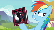 Rainbow Dash holding Shadow Spade book S8E17.png