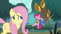 Fluttershy grins nervously as Pinkie plays music S8E18