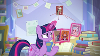 Twilight holds photos of the villains S9E25