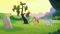 Apple farmer ponies in front of a dead tree S7E16