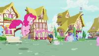 Pinkie Pie hopping up to Newspaper Pony S7E18