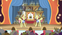 Curtain opens to reveal many bottles of tonic S4E20