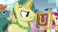 Reporter Pony with a copy of the journal S7E14