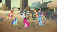 Dr. Caballeron surrounded by heroes and villagers S7E18