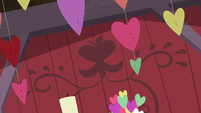 Strings of hearts hanging in the barn S8E10