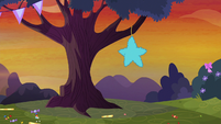 Star-shaped pinata on a tree branch S9E14