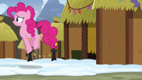 Pinkie Pie hopping away from a mud hut S7E11