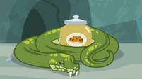 Antoine napping with his jar of snake treats S9E18