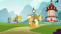 Applejack walking while carrying a bag of apples S5E19
