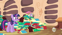 Spike peering from a pile of books S2E21