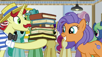 Flam holding a tall stack of books S8E16