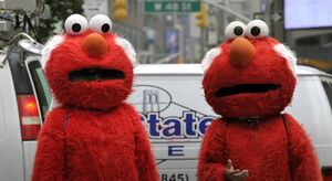Two mascots of Elmo with grey hair.