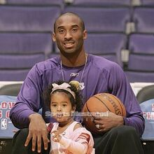 Kobe Bryant of the Lakers sits down with his daughter Natalia in between his legs.jpg