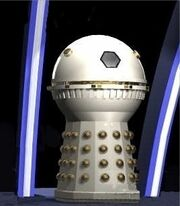 A cream-coloured Dalek with a spherical head section and no appendages. The hemispheres and detailing around the dome midsection are painted in gold.