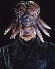 An alien creature with a vertically elongated head, small mouth, prominent chin and large exposed brain. A single grey eye is set centrally in the face, with tentacles protruding from the sides of the head. It wears a black shirt, tie and black pinstripe jacket.