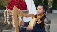 Orla playing a harp S3E30a
