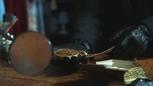 2x01 médaillon du Spectre loupe mains M. Gold gants boutique d'antiquités.png