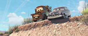 Doc and Mater taunt McQueen as he falls in a cactus patch