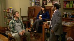Tom visting Andy and April who are conversating at the stand.