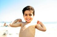 Little-boy-on-beach-showing-his-muscles