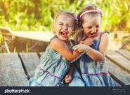 Stock-photo-two-little-girls-in-the-same-jeans-dresses-dabble-hugging-and-have-a-good-time-on-a-summer-sunny-day-619133339