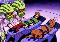 The aliens attach wires on Shaggy and Scooby which tickles