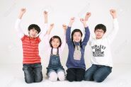 82324900-a-group-of-asian-kids-kneeling-and-handraising-isolated-on-white