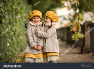 Stock-photo-two-small-twin-sisters-dressed-in-an-autumn-coat-and-yellow-hats-with-two-pigtails-are-hanging-out-740790619