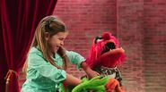 A kid tickling Kermit and Animal