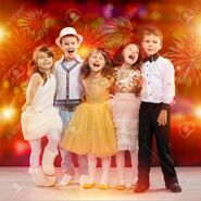 66088286-group-of-happy-kids-in-holiday-clothes-with-fireworks-on-background-holidays-christmas-new-year-xmas