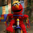 Elmo riding his tricycle