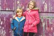 84655613-portrait-of-two-adorable-kids-outdoors-wearing-warm-coats-standing-next-to-old-purple-background