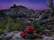 Elmo naps on a rock in Elmo in Grouchland