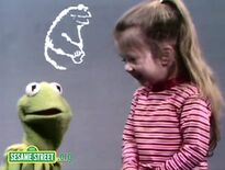 Joey laughs as she adds Cookie Monster to the alphabet